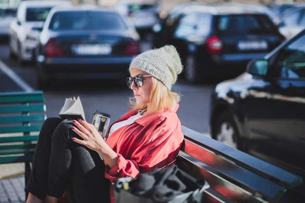 Woman with cup reading book on bench Free Photo