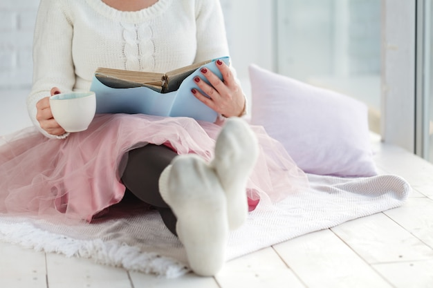Woman with cup tea rest plaid, foot with white socks Premium Photo