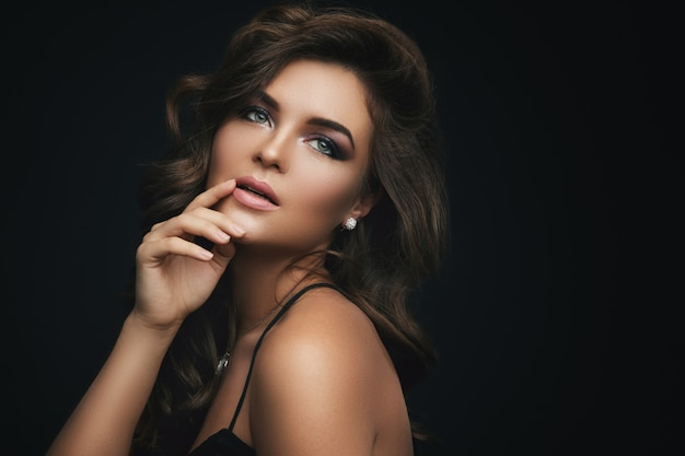 Woman with curly hair, beautiful make-up and expensive pendant with a dimond Premium Photo
