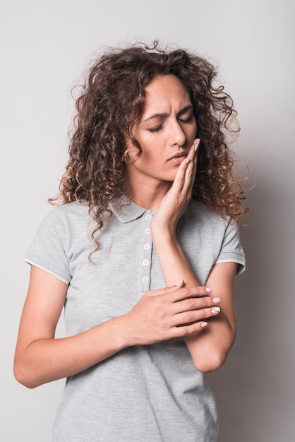 Woman with curly hair having toothache against gray backdrop Free Photo