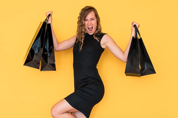 Женщина с вьющимися волосами, держащая черные хозяйственные сумки Бесплатные Фотографии