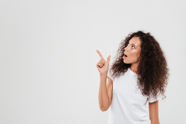 Woman with curly hair pointing finger away Free Photo