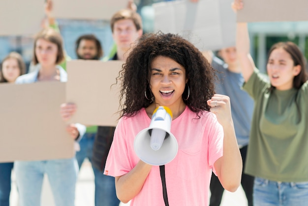 Woman with curly hair protesting with megaphone Free Photo
