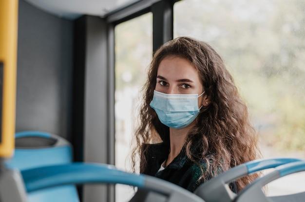 Женщина с вьющимися волосами в медицинской маске в автобусе Бесплатные Фотографии