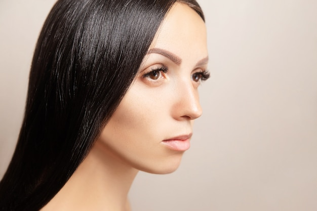 Woman with dark shiny hair and long brown extensions eyelashes Premium Photo