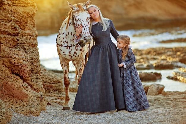 Женщина с дочерью и пятнистой лошадью Premium Фотографии