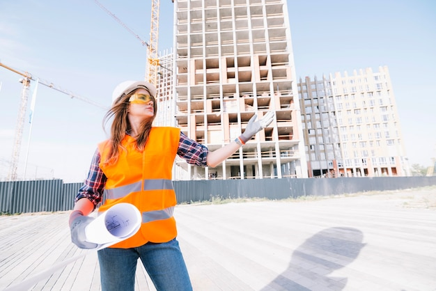 Woman with draftgesturing on construction site Free Photo