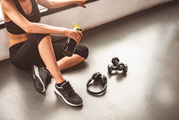 Woman with dumbbell and device exercise lifestyle workout in gym fitness breaking relax Premium Photo