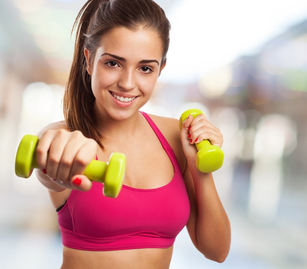 Woman with dumbbells in a shopping center Free Photo