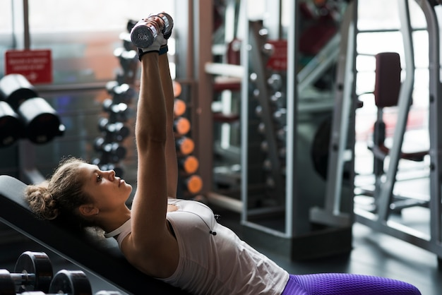 Woman with dumbbells lying on bench Free Photo