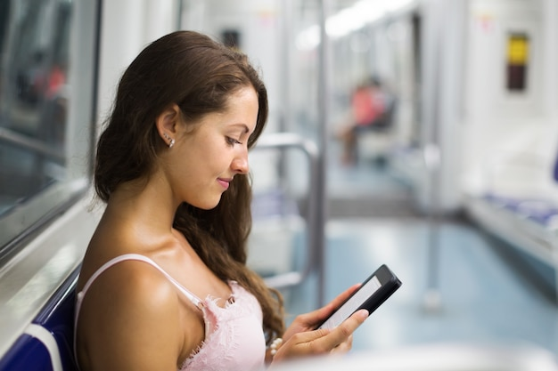 Woman with ereader in subway train Free Photo