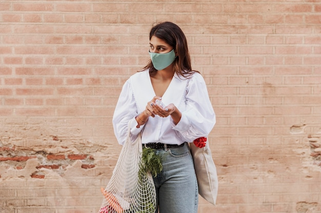 Женщина с маской для лица и продуктовыми пакетами, использующая дезинфицирующее средство для рук Бесплатные Фотографии