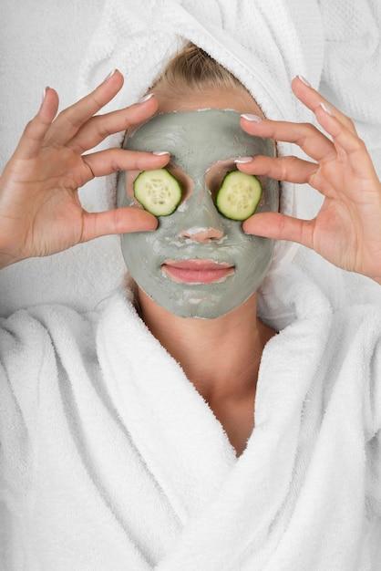 Donna con maschera facciale e fette di cetriolo Foto Gratuite