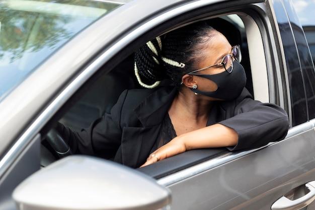 Donna con maschera facciale guardando dietro mentre si guida la sua auto Foto Gratuite