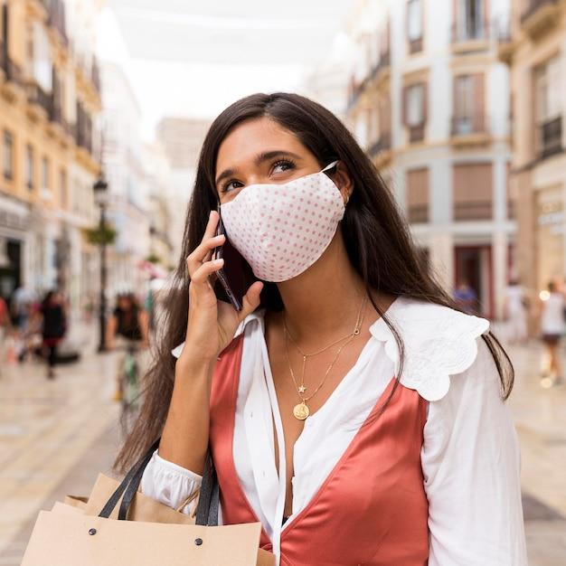 Женщина с маской для лица разговаривает по телефону Бесплатные Фотографии