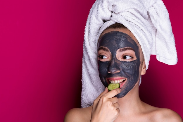 Woman with face mask tasting cucumber Free Photo