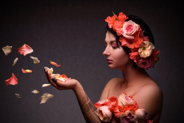 Woman with a floral wreath and rose petals in her hands Premium Photo