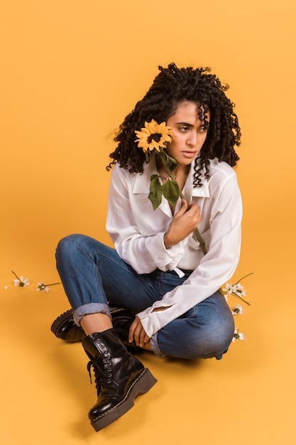 Woman with flower sitting on floor Free Photo