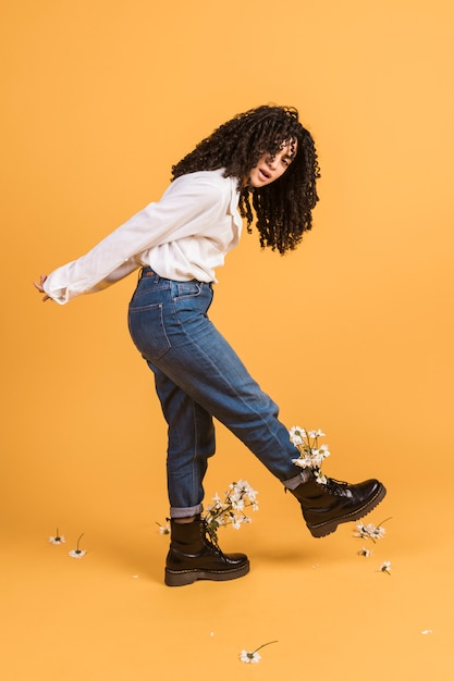 Woman with flowers in boots raising foot Free Photo