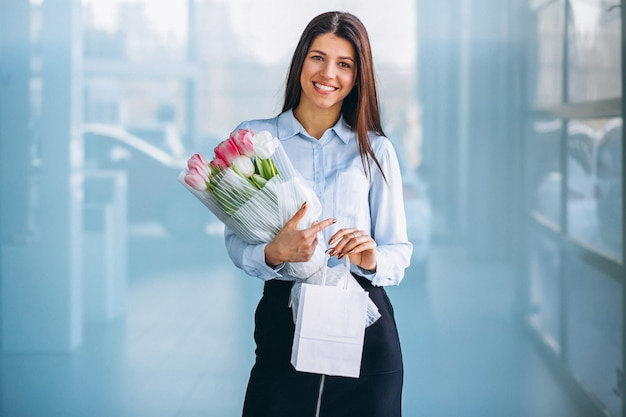Woman with flowers in a car showroom Free Photo