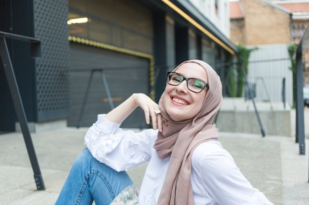 Woman with glasses and hijab smiling Free Photo