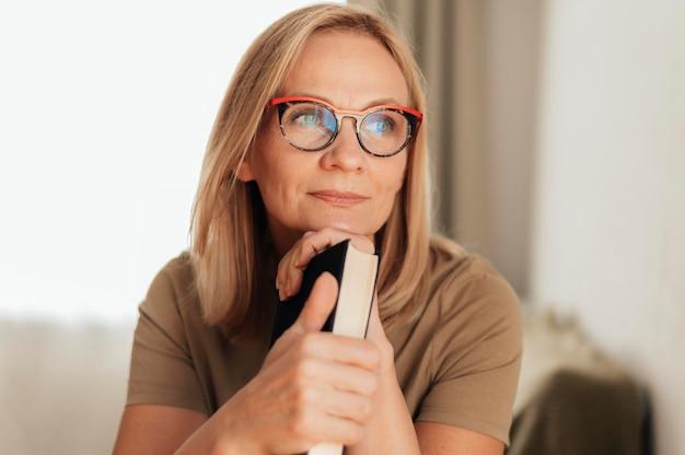 Donna con gli occhiali a casa che tiene il libro durante la quarantena Foto Gratuite