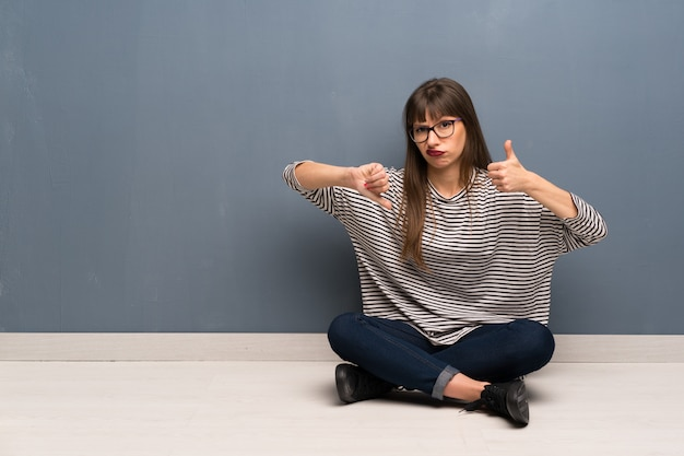 Woman with glasses sitting on the floor making good-bad sign. undecided between yes or not Premium Photo