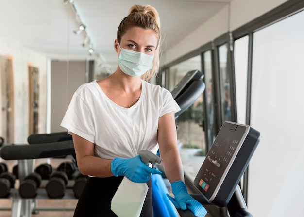 Donna con guanti pulizia attrezzature da palestra durante la pandemia Foto Gratuite
