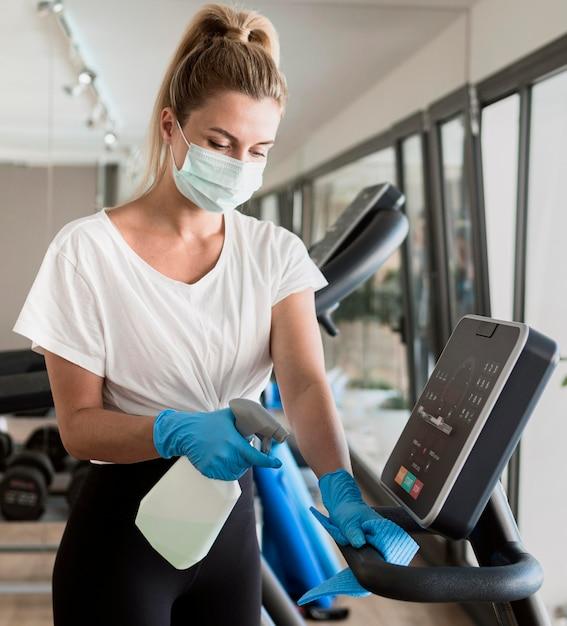 Donna con guanti pulizia attrezzature da palestra mentre indossa la mascherina medica Foto Gratuite
