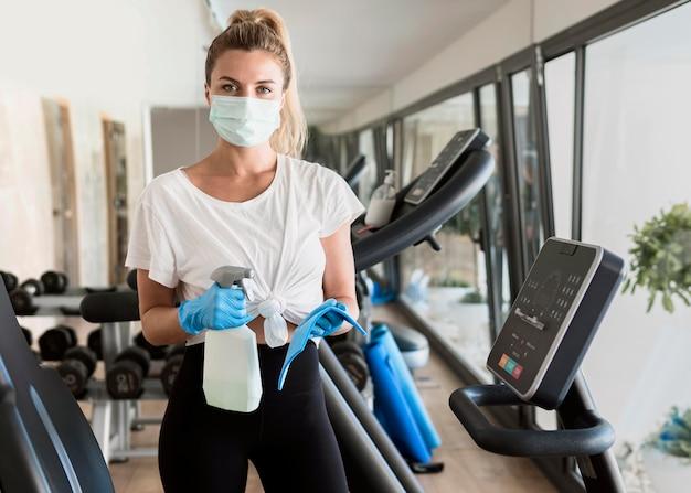 パンデミック時に医療用マスクでジム設備を掃除する手袋をした女性 無料写真