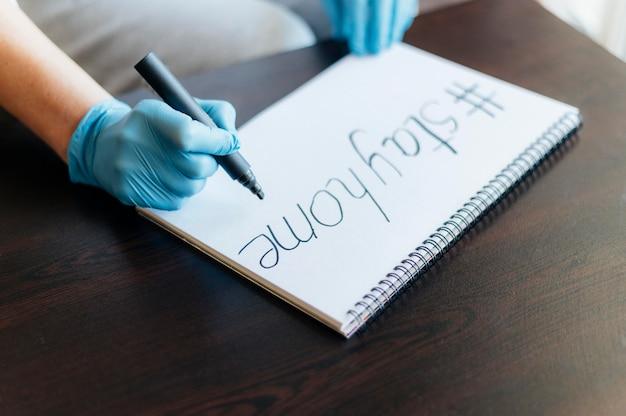 Donna con guanti che scrivono sul taccuino Foto Gratuite