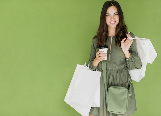 Woman with green handbag and coffee on green background Free Photo