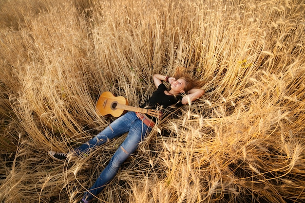 Woman with a guitar lying in the wheat field Premium Photo