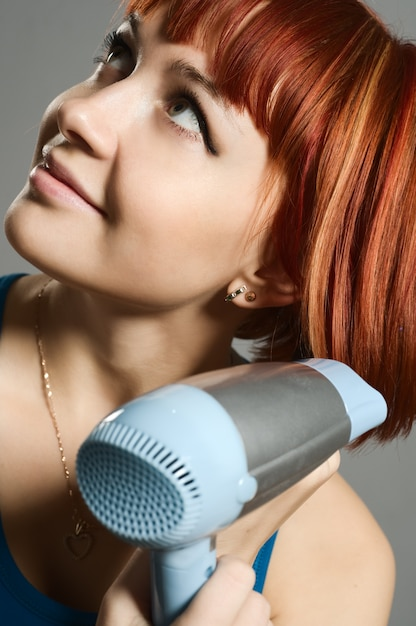 Woman with hairdryer and a hairbrush Free Photo