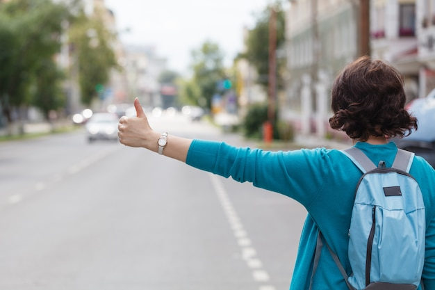 Woman with handbag hailing a taxi cab walking in city street Premium Photo