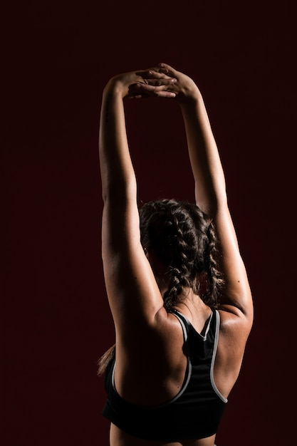 Woman with hands in air and dark background from behind shot Free Photo