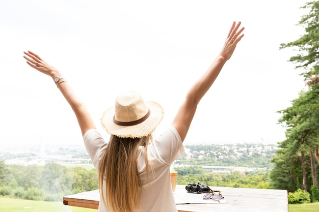 Woman with hands in the air from behind Free Photo