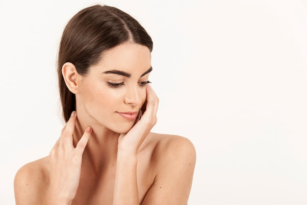 Woman with hands on her neck and looking down Free Photo