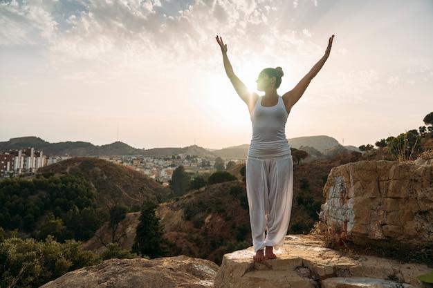 Donna con le mani in su durante la sessione di yoga Foto Gratuite