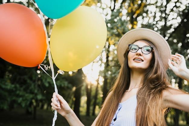 帽子と公園で風船を持つ女性 無料写真