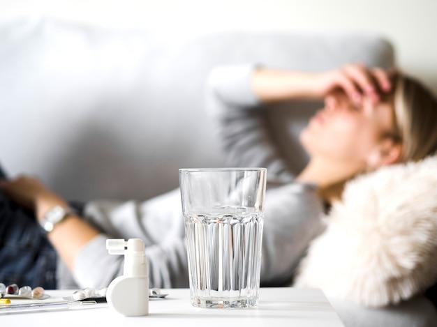 Женщина с головной болью на диване Premium Фотографии