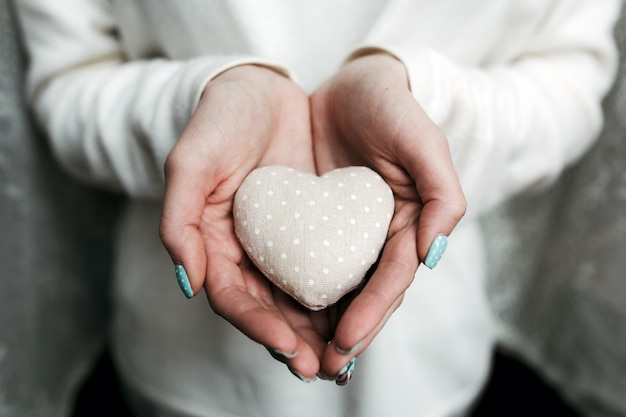 Woman with a heart-shaped stone in hands Free Photo