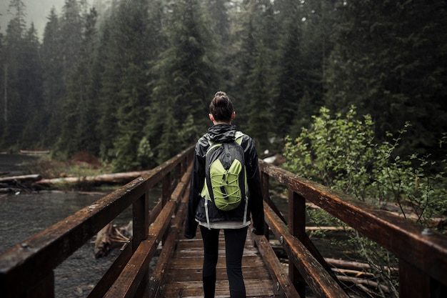 Woman with her backpack standing on wooden bridge Free Photo