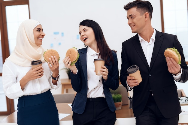 A woman with her colleagues eating a hamburger. Premium Photo