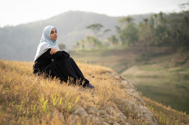 Woman with hijab sitting outdoor Premium Photo