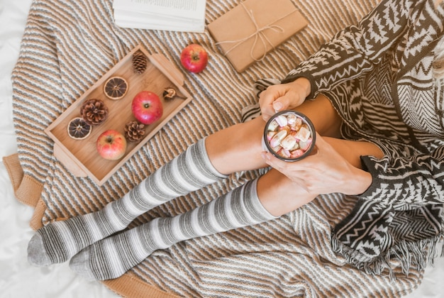 Woman with hot chocolate relaxing on bed Free Photo