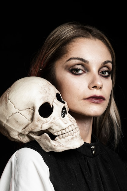 Woman with human skull on shoulder Free Photo