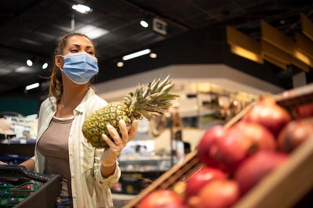 코로나 바이러스 기간 동안 과일을 구입하고 유행성 격리를 준비하는 식료품 점에서 위생 마스크와 고무 장갑 및 장바구니를 가진 여성 무료 사진