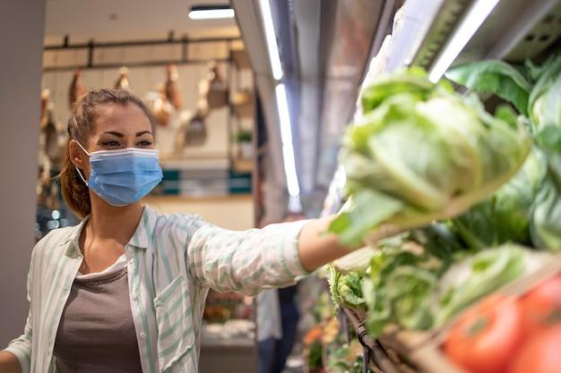 Donna con maschera igienica e guanti di gomma e carrello della spesa in drogheria acquistare verdure durante il virus corona e prepararsi per una quarantena pandemica Foto Gratuite