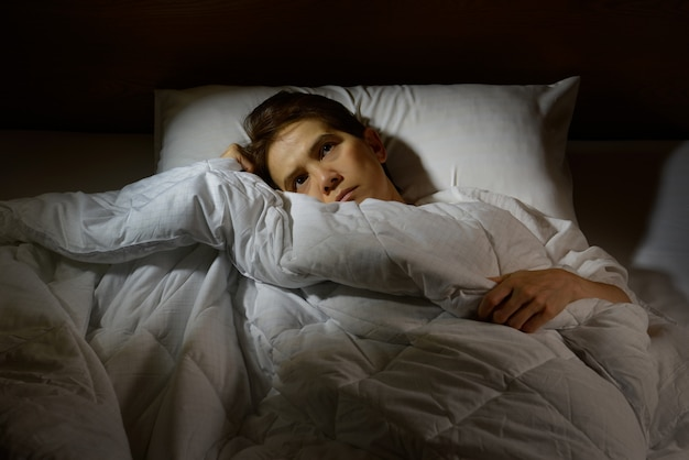 Woman with insomnia lying in bed with open eyes Premium Photo